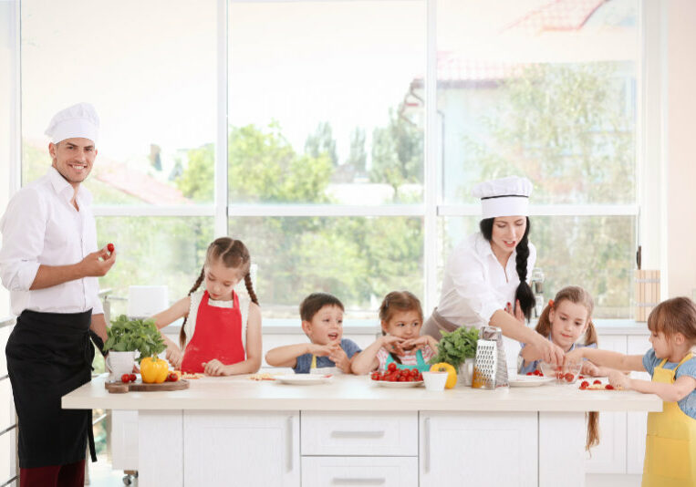 Two chefs and group of children during cooking classes