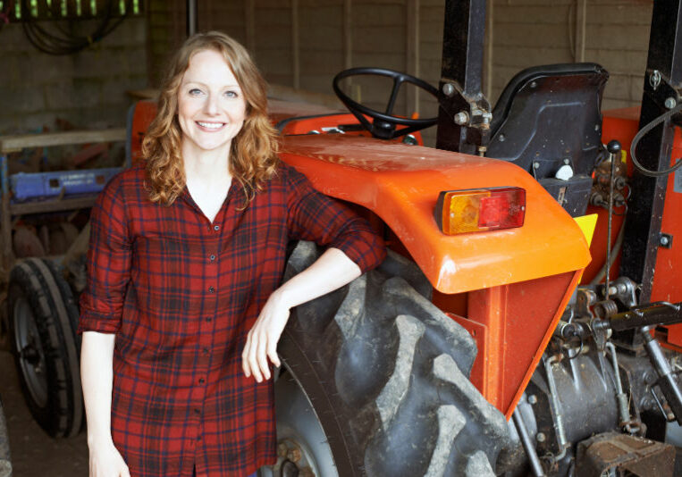 Portrait Of Female Agricultural Worker With Tractor